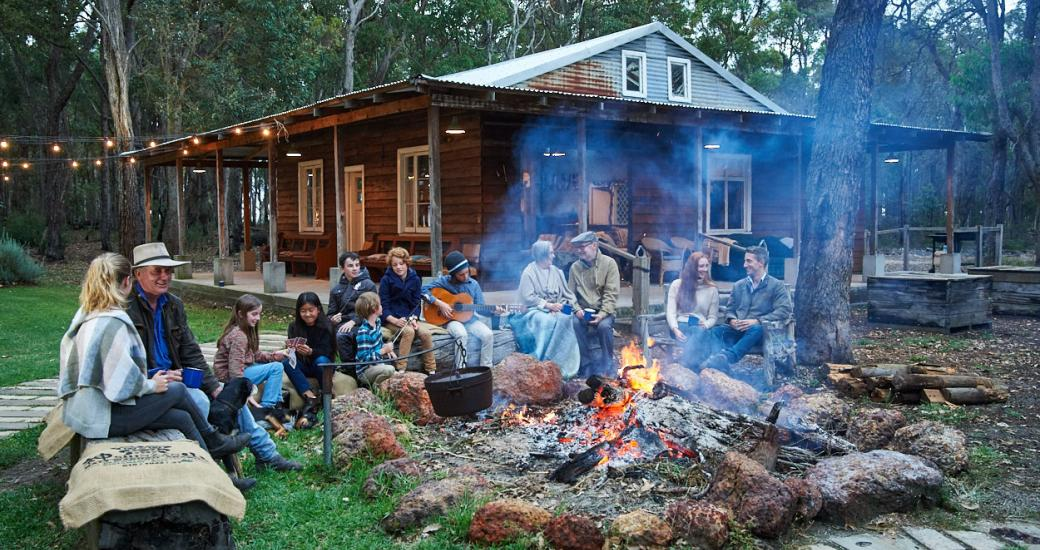 Group of family and friends sit around a bonfire and cabin in Margaret River