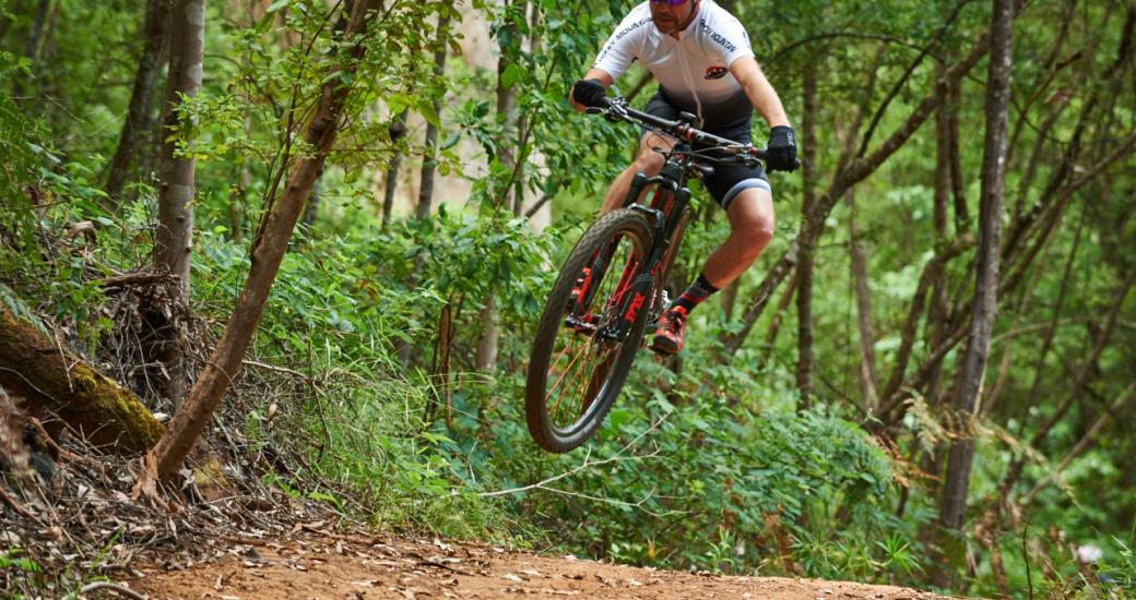 Boy does a jump on a mountain bike in green forest in Australia's South West