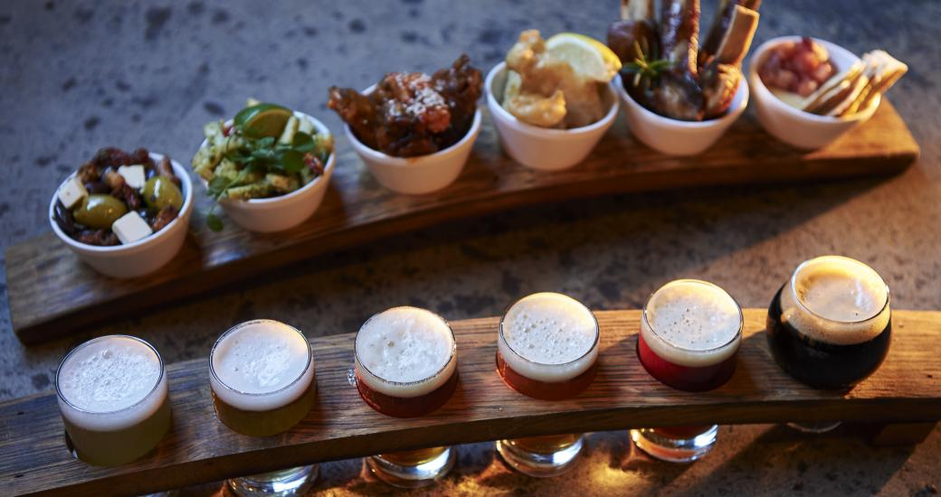 A paddle of beer for tasting paired with food