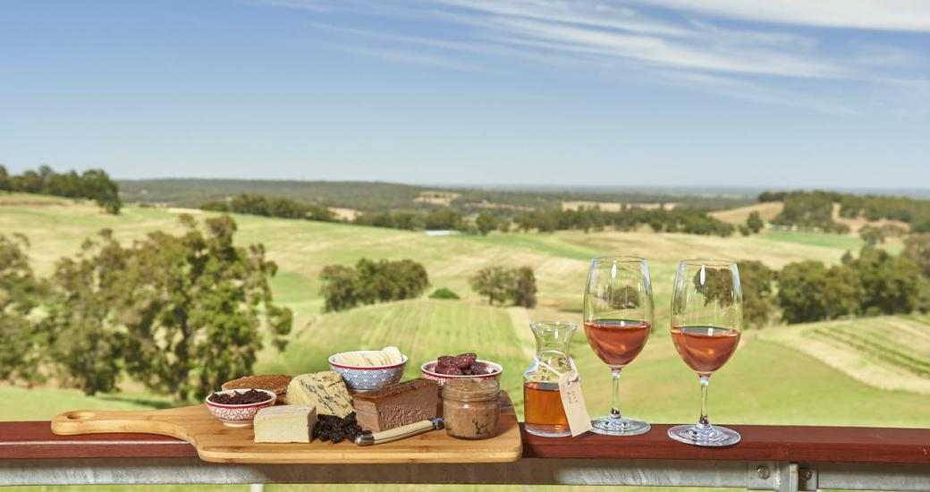 Wine and cheese spread on a ledge with vineyard in the background