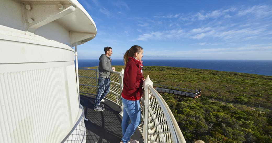 A landscape image of two people socially distanced standing on the top of a lighthouse lookout towards the ocean to show safe tours in Australia's South West