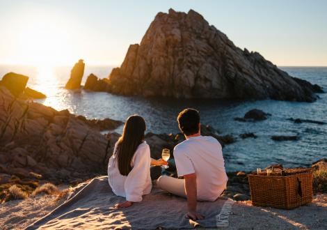 A couple share a glass of wine in front of Sugarloaf Rock at sunset