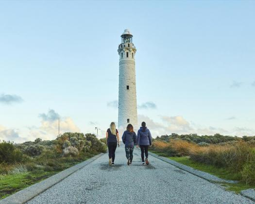 Three people walk towards Cape Leeuwin Lighthouse