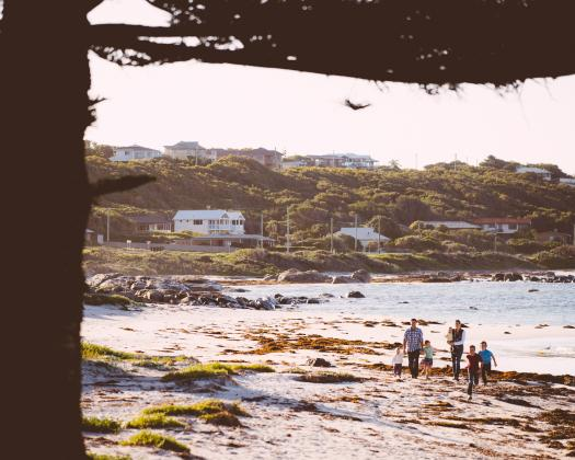 A family walk along a beach with Flinders Bay Caravan Park in the background