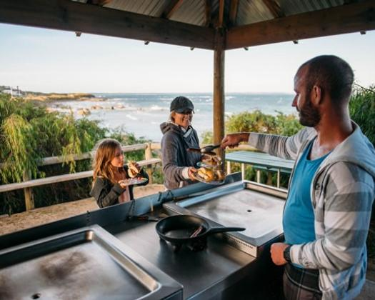 two kids get served a sausage on the barbecue with a view of the ocean at Flinders Bay Caravan Park