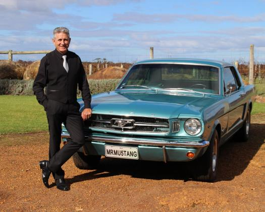 A man stands next to a blue mustang used for Mr Mustang Hire