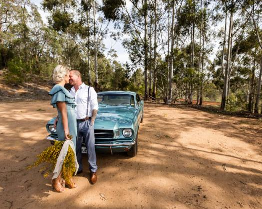 A happy newlywed couple stand in front of The Mr Mustang car in Boranup Forest