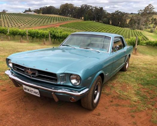 A blue Mustang from Mr Mustang Hire in front of a vineyard
