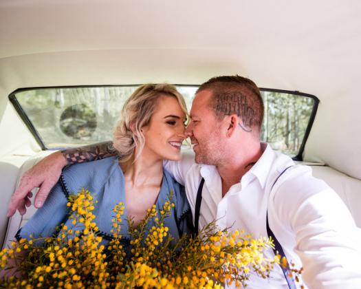 A happy couple close together inside Mr Mustang Hire car with flowers