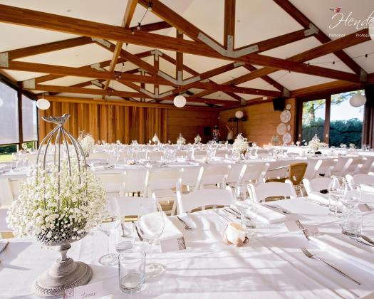 Inside Saint Aidan Wines barn are tables set up for a wedding