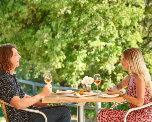 A couple sit in front of vines at Saint Aidan Winery dining on wine and cheese