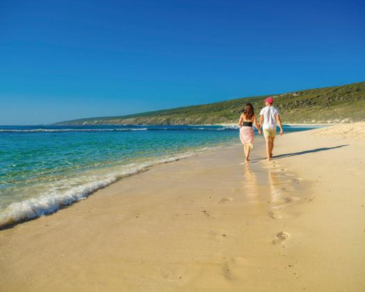 Couple walking along Yallingup Beach on luxury tour