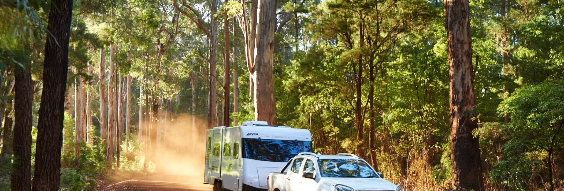 Car tows motorhome on gravel road in forest in Australias South West