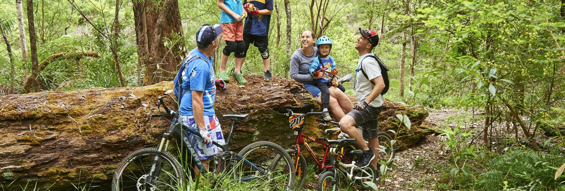 A group of adults and kids rest on a log with mountain bikes