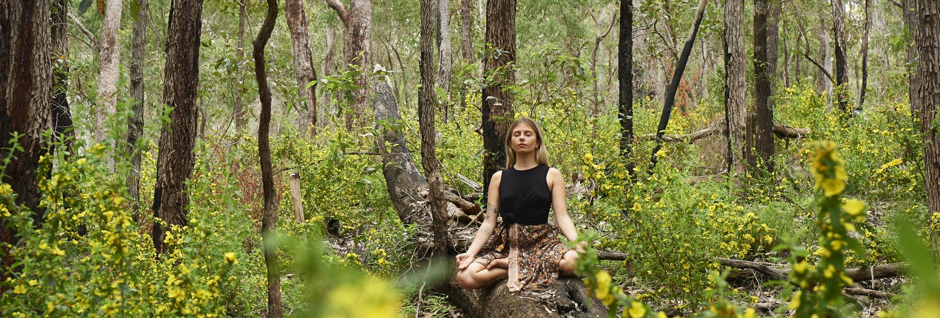 A girl sits cross legged meditating in a lush green forest
