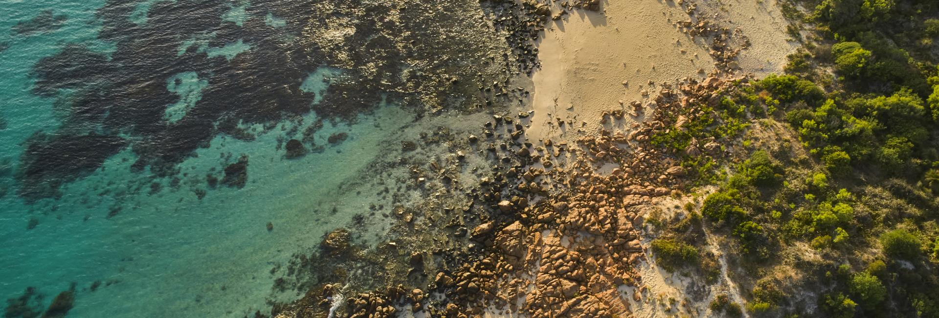 Drone aerial of turquoise ocean, red rocks, and green bushland