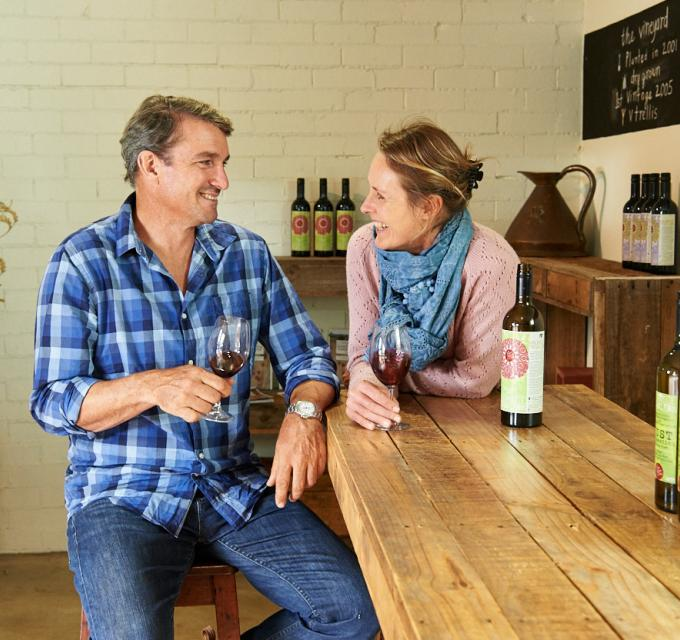 Husband and wife share a glass of wine in a cellar door