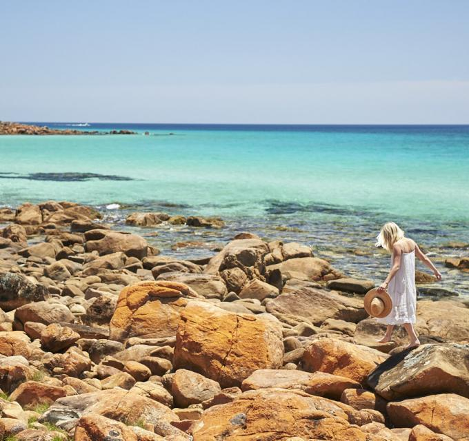 A girl in a white dress walks along rocks next to bright blue ocean