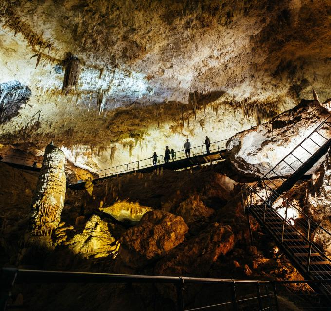 Group of people walk along staircase inside Jewel Cave