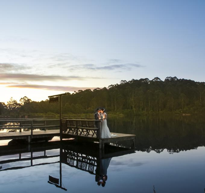 A bride and groom stand on a jetty with reflective water at sunset