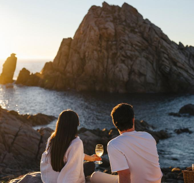 a couple enjoy a glass of wine on the coast with Sugarloaf Rock in the background